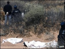 Members of the Mexican Federal Police, inspect in the surroundings of an unmarked grave, in Ciudad Juarez, Mexico, on March 14, 2009