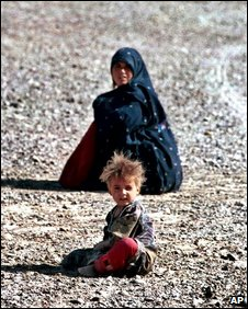 An Afghan boy and a woman sit at an Iranian refugee camp