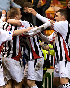 Dunfermline players mob Graham Bayne after his winning penalty