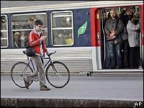 Ciclista pasa frente a tren lleno de pasajeros en Francia