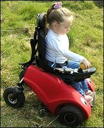 Photo of a young girl driving her Wizzybug across grass