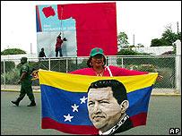 Mujer parada frente al puerto de Maracaibo sostiene bandera con la imagen de Hugo Ch�vez