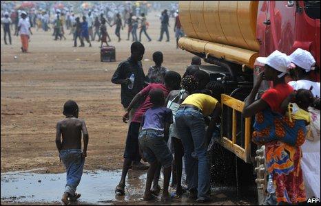 Angoolan children gather at a water truck