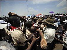 A woman is carried over crowds to medical attention