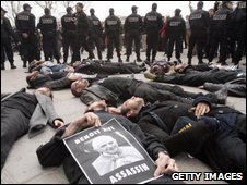 Left-wing activists are guarded by French police as they lie down in protest against Pope Benedict's opposition to condoms