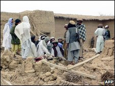 Armed tribesmen gather at the site of a suspected US missile strike at Jani Khel, northwest Pakistan 16 March, 2009