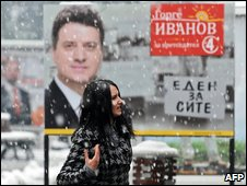 A woman walks past a poster of George Ivanov in Skopje