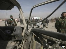 Soldiers of Afghan National Army looks at the damaged vehicle after an explosion in the outskirts of Kabul, Afghanistan, Sunday, March 15, 2009.