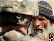 A US soldier (L) belonging to the NATO-led International Security Assistance Force (ISAF) talks with an Afghan man during a patrol outside Bagram airbase, 50 kms north of Kabul on February 28, 2009