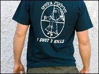 شخص يعرض قميصا عليه عبارة طلقة واحدة قتيلان