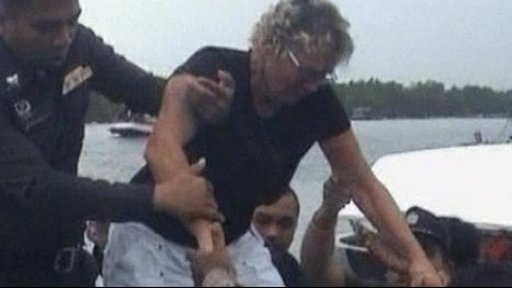 Linda Robertson is helped from the yacht by police