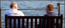 A retired couple sit by the sea