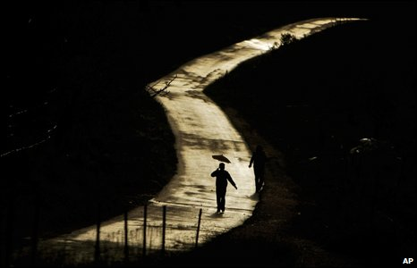 A Palestinian with an umbrella walks along a deserted road in Ramallah