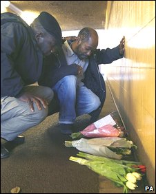 Ian's brothers Barry (Right) and Cleave Newtion kneel beside flowers left in the underpass