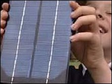 Child holding solar photovoltaic panel
