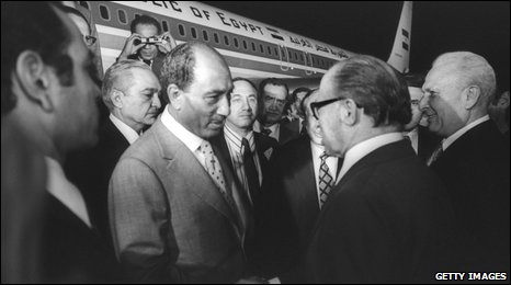 Anwar Sadat flies to Israel and is met by Menachem Begin