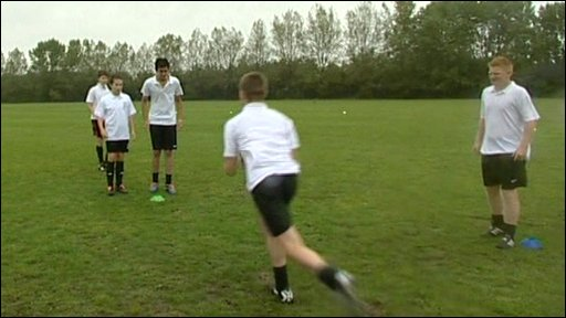 Pupils playing rugby on a playing field