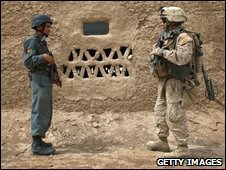 An Afghan policeman (left) and a US soldier on patrol near Bakwa, Afghanistan, 26 March