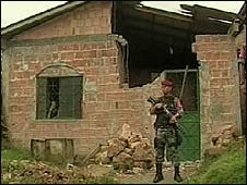 Soldier in front of a house damaged by falling aircraft parts in Manaus, Brazil (26/03/2009)