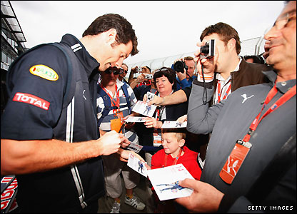Red Bull's Australian driver Mark Webber is mobbed by fans as he arrives at Melbourne's Albert Park on Friday