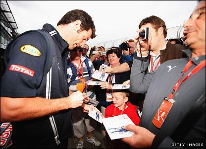 Red Bull's Australian driver Mark Webber is mobbed by fans as he arrives at Melbourne's Albert Park on Friday