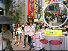 Japanese shoppers walk through the Shibuya district of Tokyo
