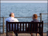 Pensioners sitting on a bench at the seaside