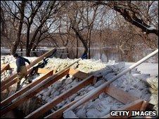 A volunteer helps build a dyke near a home