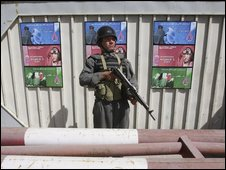Afghan policeman stands guard in front of the fortified gate of the Afghan Ministry of Women's Affairs on 8 March