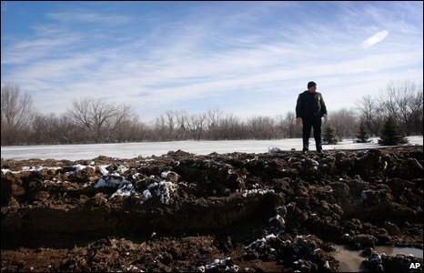 Fargo Police Detective Paul Lies stands on top of a levee, 28/03