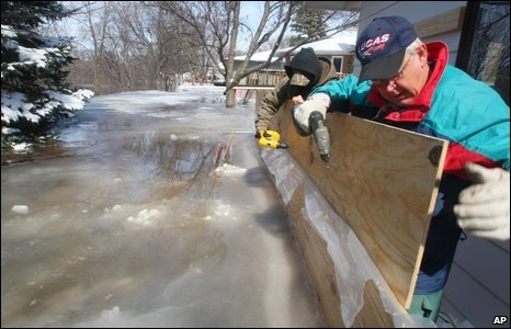Chad Swanson (L) and Ralph Henning work on a plywood dyke in Moorhead, 28/03