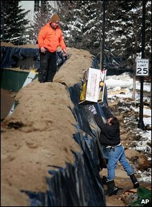 Fargo residents pass supplies over the levee, 28/03