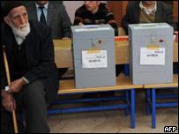 Мужчина рядом с избирательными урнами