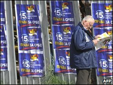 "A man walks past campaign posters advertising ""Rights for Serbs"" in Montenegro's capital Podgorica, 28 March 2009"