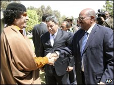 Libyan leader Col Gaddafi (L) greets President Bashir in Libya on 26 March 2009