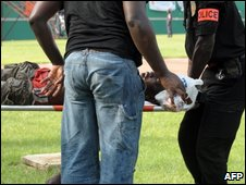 Police carry an injured person at Felix Houphouet-Boigny stadium in Abidjan on 29 March 2009