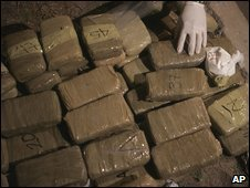 A federal police officer arranges packages of marijuana and a bag of cocaine seized in a house allegedly occupied by drug dealers during an operation in Ciudad Juarez, Mexico, Monday 9 March 2009
