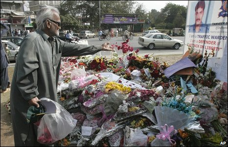 A man lays flowers at the spot of the attack on the visiting Sri Lankan cricket team in Lahore, Pakistan, on 6 March, three days
