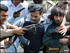 Security officials arrest a suspected militant in Lahore, 30 March 2009