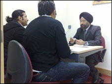 Harpal Singh, manager of the Southall branch of the Punjab National Bank talks to customers
