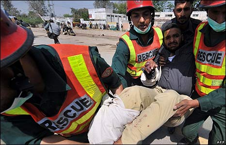 Injured policeman carried to an ambulance outside the police academy near Lahore on 30/3/09