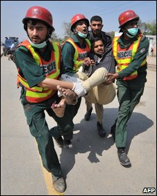 Rescuers carry a wounded policeman from the attack scene in Lahore, 30 March