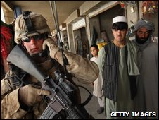 Afghans watch as a US marine patrols a bazaar in Delaram, Afghanistan, 27 March