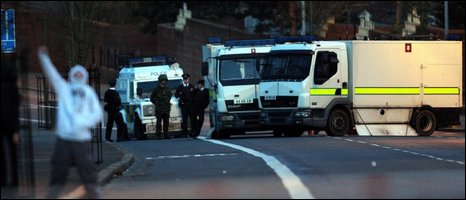 Army bomb disposal experts monitor an abandoned and burnt out van on the Crumlin Road in Belfast