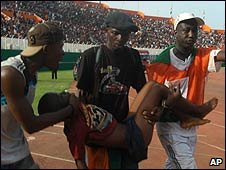People carry an injured person after a stampede at a football stadium in  in Abijdjan, Ivory Coast ( 29 March 2009)