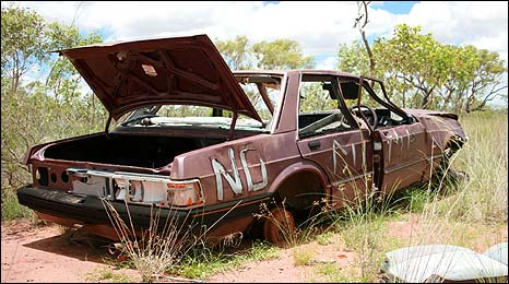 Wrecked car emblazoned with words NO DUMP