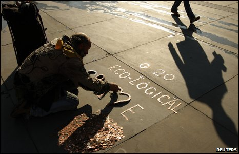 A demonstrator makes an anti-G20 sign out of coins at Trafalgar Square in central London