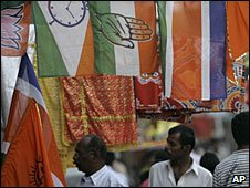 People walk past shop selling politcal party flags in Mumbai, 2 March 2009