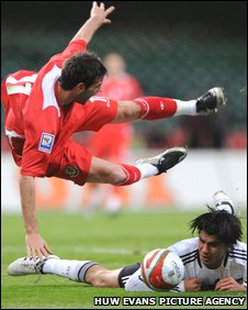 Germany's Serdar Tasci sends Joe Ledley sprawling in the area