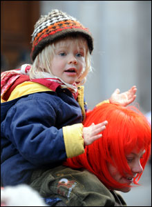 Child on shoulders of protester